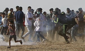 Volunteer paramedic Razan al-Najjar, 21, centre, is seen before being shot by Israeli troops while running to take cover from teargas.