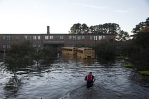 A volunteer firefighter makes his way through floodwaters in North Carolina caused by rain from Hurricane Matthew to turn off the lights of a school bus