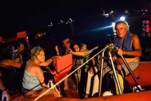 Rescuers and volunteers help local people evacuate from the village of Mati