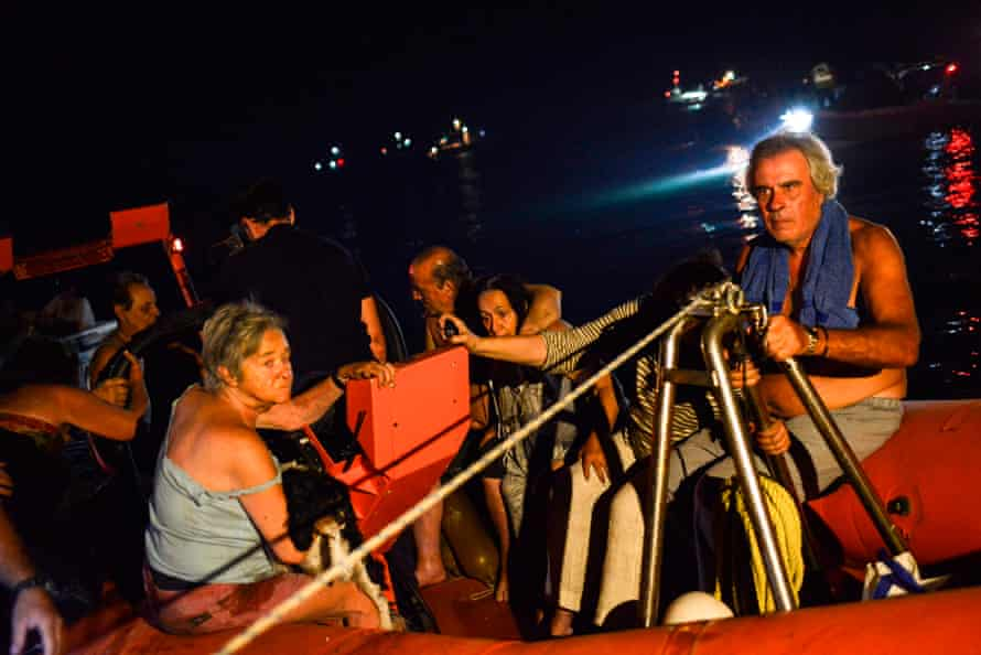 People evacuate from the village of Mati on Monday night