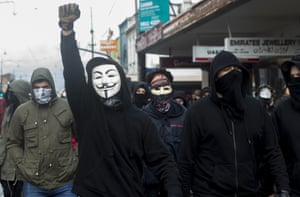 Anti-fascist protestors wearing masks and hooded tops march down the main street in Coburg during a 'Say no to racism' protest and a counter 'Stop the far-left' rally in Melbourne on Saturday.