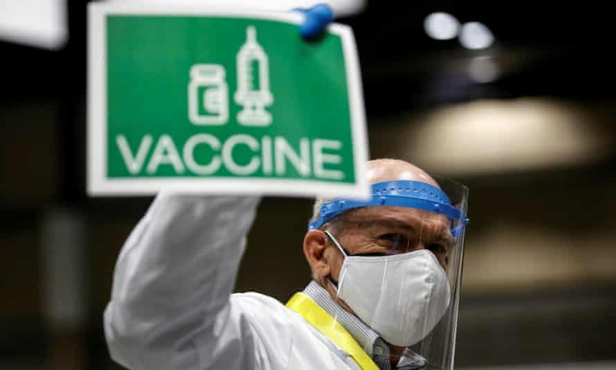 A doctor holds up a sign to signal his station needs more vaccine doses at Lumen Field Event Center in Seattle.