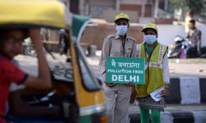 Volunteers stand with placards at a junction in Delhi to raise awareness of odd-even number plate car restrictions.