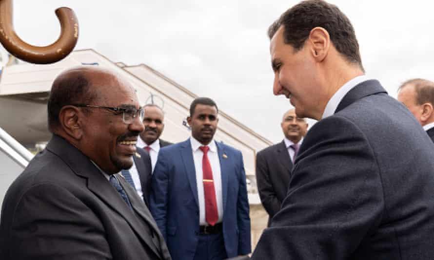 Sudan's president, Omar al-Bashir, shaking hands with Bashar al-Assad