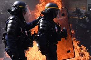 Paris, France. Riot police walk past a burning barricade as they clash with protesters. More than 7,400 officers have been deployed across the city with orders from the president to take an extremely firm stance against violence