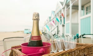 Bottle of champagne and champagne flute in picnic basket, Southwold, Suffolk, UK.