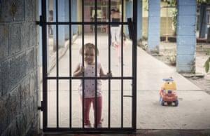 A baby plays behind bars