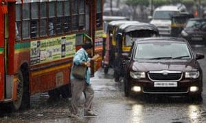A man tries to cross a street amid busy traffic in the rain in Mumbai.