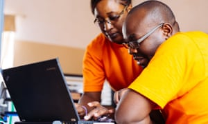 Marie-Reine Rutagwera, Malaria Surveillance Specialist for MACEPA, and a man, Monde Mathews, Environmental Health Officer for Gwembe district, reviewing malaria surveillance data on a laptop computer