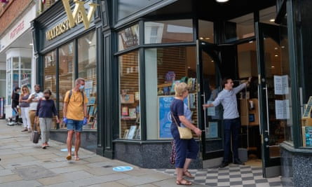 Customers queue to enter a Waterstones shop in Guildford, Surrey that reopened on 15 June.