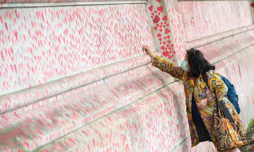 A woman writes a message on the Covid Memorial Wall in Westminster, London