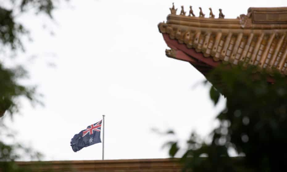 File photo of the flag on top of Parliament House seen over the roof of the Chinese embassy in Canberra