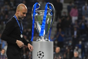 Manchester City's Spanish coach Pep Guardiola walks past the trophy he was brought to the club to win.