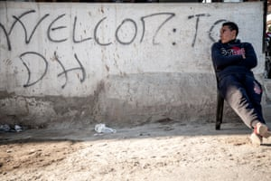 A man in Douar Hicher, Tunisia, sits in front of a sign saying 'Welcome to DH'