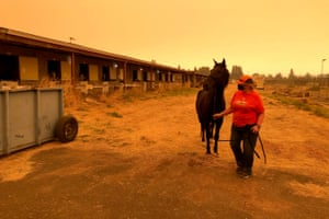Catherine Shields, of Silverton, Ore., leads her horse Takoda under smoky skies, on the Oregon State Fairgrounds, Wednesday, Sept. 9, 2020, in Salem, Ore. Shields evacuated the horse and other animals from her home on Tuesday, as a wildfire threatened. Hundreds of horses have been brought to the fairgrounds in Salem by people fleeing the fires, along with llamas, goats and other animals. The Red Cross is helping people at the fairgrounds, which has been turned into an evacuation center.