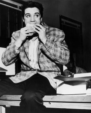 Presley enjoys a snack on a bench in Memphis, Tennessee, 25 March 1958