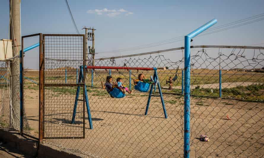 Children play on swings in Camp Roj
