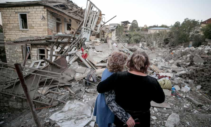 Two women embrace as they examine the ruins of a residential house destroyed in a shelling attack in Stepanakert, Nagorno-Karabakh
