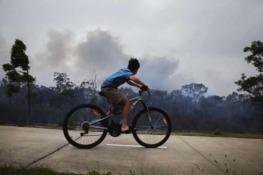A boy on a bike looks on as a fire smoulders at Voyager Point in Western Sydney.