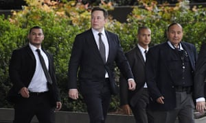 Elon Musk, second from left, arrives at a Los Angeles court for his defamation trial.
