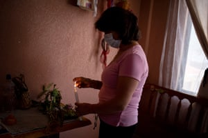 Marta Jaque lights a candle to the saints on her home altar during Easter Sunday in Quito, Ecuador, 5 April