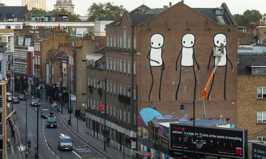 Cleaning up … Stik applies the finishing touches to his work Past, Present and Future in Old Street, east London. Photograph: David Levene for the Guardian