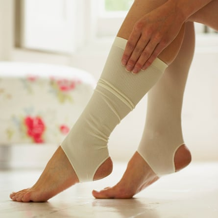 A woman putting on a compression stocking