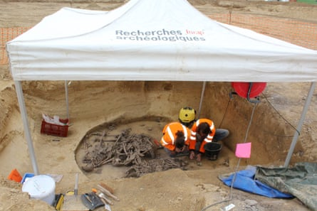 Researchers examine human remains at the massacre site.