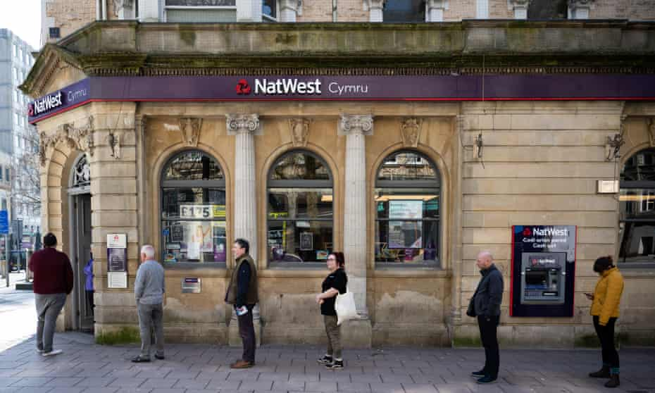 Customers observe social-distancing rules as they queue for the bank in Cardiff.