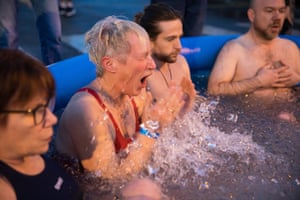 A woman emerges from the ice during the ice bath.