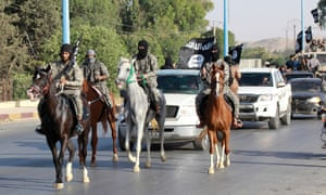 Isis fighters parade through Raqqa after its capture in June 2014.