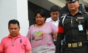 Patnaree Chankij, the mother of an anti-junta activist, is escorted by police as she leaves a military court in Bangkok.