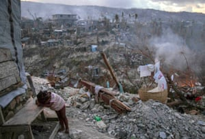 A child rests near collapsed homes on top of a hill in Jérémie