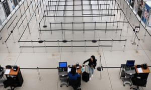 People walk through a sparse international departure terminal at John F Kennedy airport in New York on 7 March.