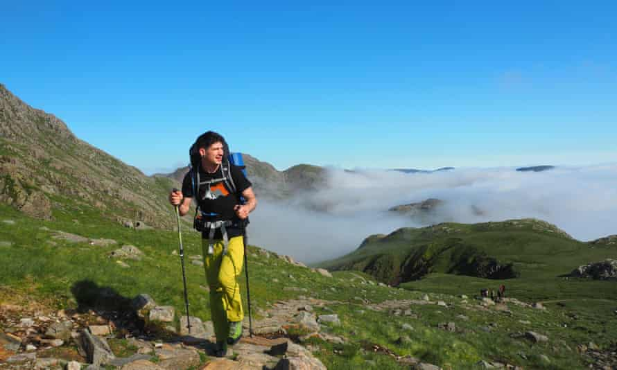 Hiker amid louds lifting the morning after a wild camp in the Lake District fells