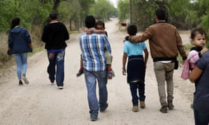 A group of migrant families walk from the Rio Grande near McAllen, Texas, on 14 March.