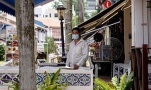A man stands in the al fresco dining area of his restaurant situated in the Kampong Glam cultural district of Singapore.
