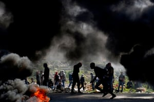 Palestinian demonstrators from Birzeit University take cover from Israeli forces in Ramallah, near the Jewish settlement of Beit El in the occupied West Bank.