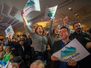 Gabierla Martinez (L) and Cesar Delgado (R) both of Lakewood, Colorado, cheer on Democratic gubernatorial candidate Jared Polis as he speaks at his midterm election night party in Denver, Colorado U.S.