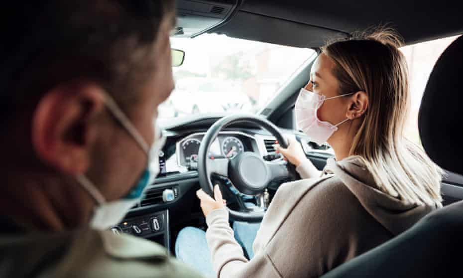 A woman with a man in a car both wearing face-masks during a driving lesson