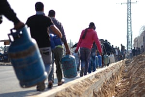 Residents of Gaza wait in line to fill up their propane tanks