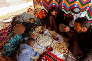 Mohsen Farhan eating with his family in a tent in the desert