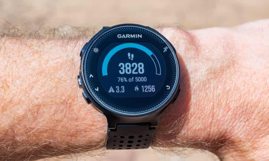 Garmin Smart Watch on male wrist displaying a step counter, distance traveled in kilometers and amount of calories burned