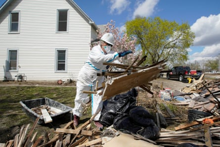 A volunteer helps clean a flood-damaged house in Pacific Junction, Iowa.
