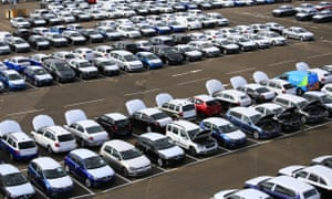 Rows VW cars in a vehicle park awaiting distribution to suppliers