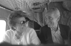 Peres and his wife on a plane, smiling at each other
