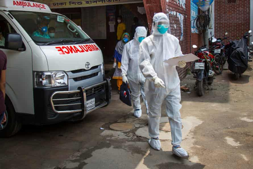 Masked health workers in white protective suits in the street