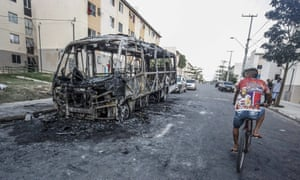 A man riding a bicycle in front of a bus burned during an attack in Fortaleza.