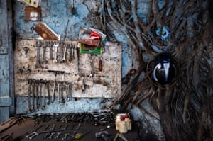 A tree grows beside mechanics' tools in an auto workshop in Mumbai