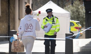 A woman brings a flower to the scene in Hackney in east London where a man died after being stabbed.